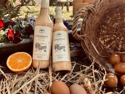 Hennenmilch Eierikör mit Eiern und Orange im Garten